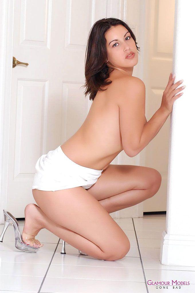 Девушка латинской внешности в белоснежной мини-юбке топлесс Megan Jones наклоняется и стягивает с себя свои розовые танга